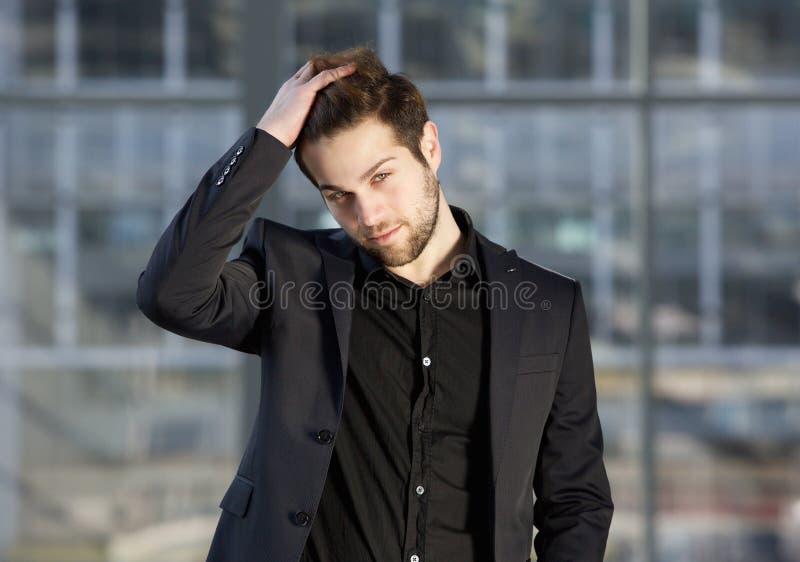 Mannequin masculin beau posant avec la main dans les cheveux photos stock