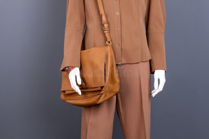 Mannequin mit brauner Kleidung und Tasche stockbilder