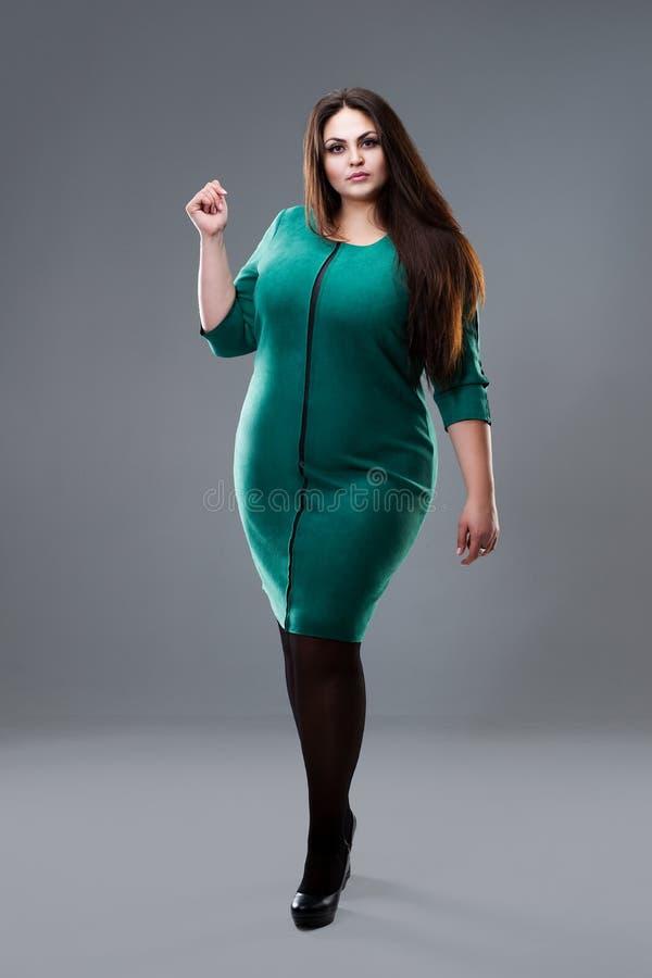 Mannequin plus de taille dans la robe verte, grosse femme sur le fond gris de studio, concept positif de corps photos libres de droits
