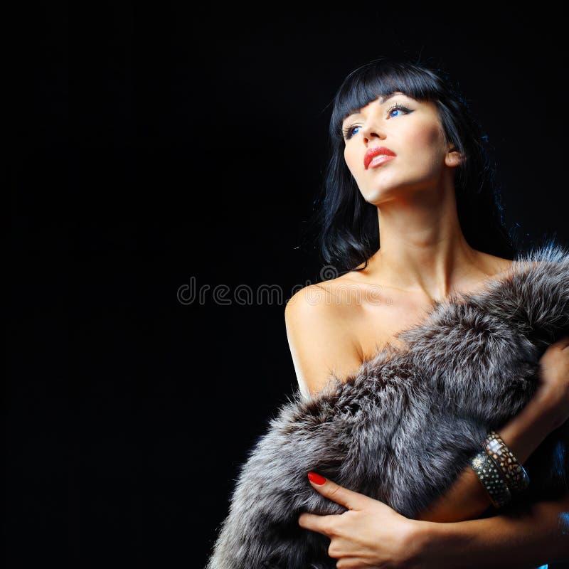 Mannequin posant à la fourrure de port de studio et regardant le copysp photos stock