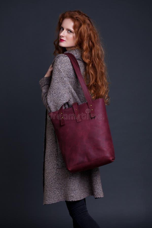 Mannequin rouge de cheveux tenant le grand sac en cuir photos stock