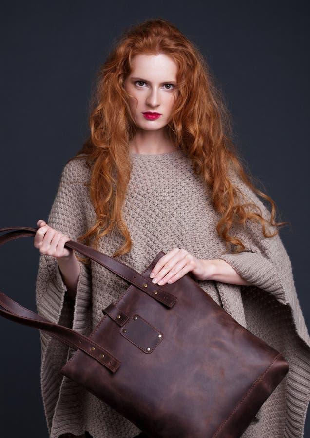 Mannequin rouge de cheveux tenant le grand sac en cuir photo libre de droits