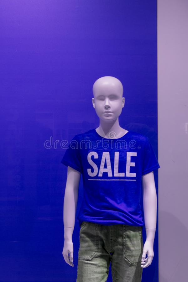 Mannequin in a row wearing blue T-shirts with the word `SALE`. royalty free stock photography