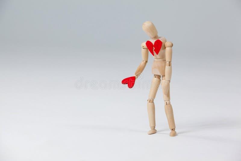 Mannequin schaut unten zu ihrem eben gefundenen ausgebesserten Herzen lizenzfreie stockfotografie