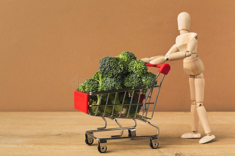 Mannequin with shop cart full of broccoli. On brown background. Advertising of food products. Shopping, healthy eating concept stock image