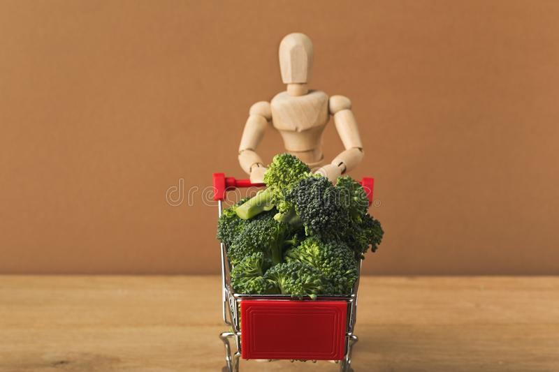 Mannequin with shop cart full of broccoli. On brown background. Advertising of food products. Shopping, healthy eating concept stock photos