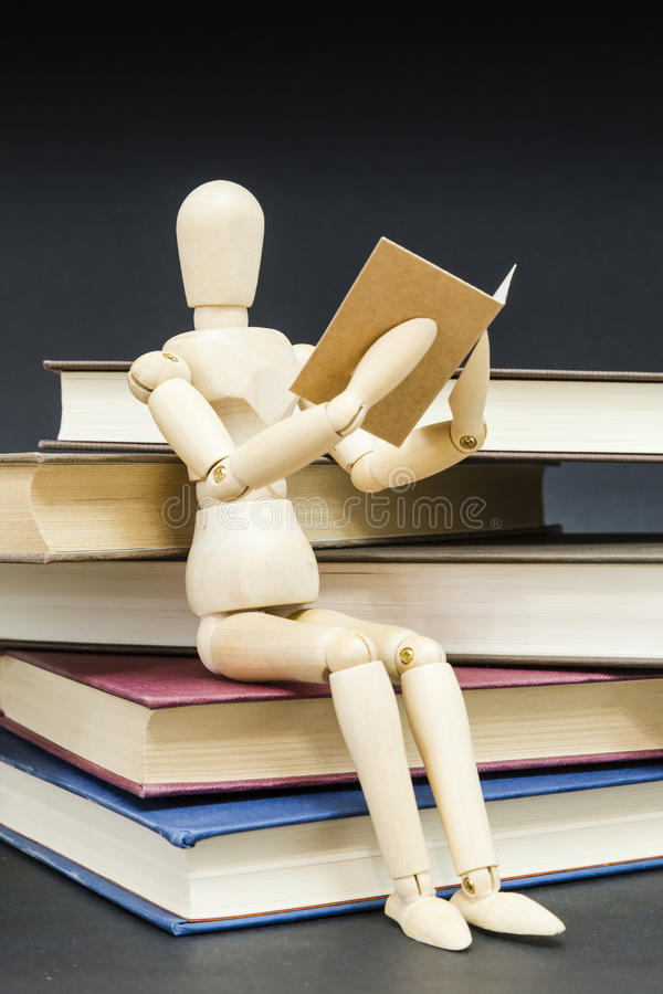 Mannequin sitting on a mountain of reading books royalty free stock image