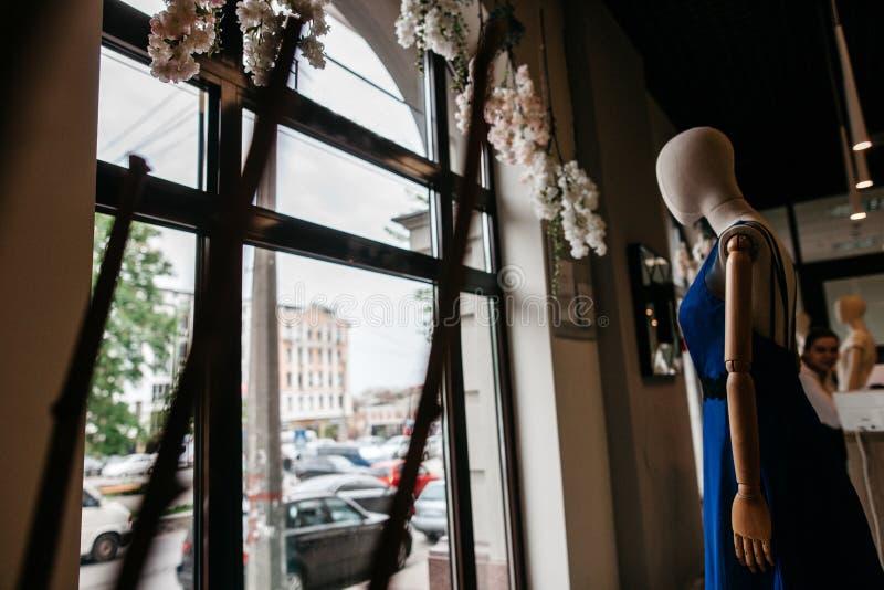 Mannequin ubierał w błękitnej smokingowej pozycji blisko okno sklep odzieżowy obrazy royalty free