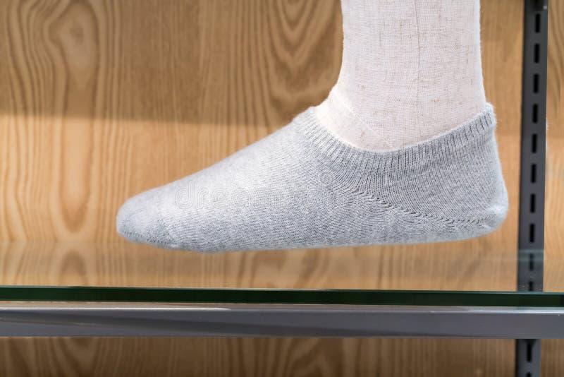 Mannequinbein, das graue Baumwollsocke und -stellung auf Glas-MIR trägt lizenzfreies stockbild