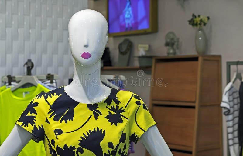 Mannequinfrau in einem gelben Kleid Weibliche Attrappe mit Sommerkleidung in einem Showfenster des Geschäftes stockfoto
