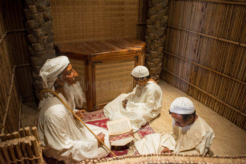 Mannequins depicting scene of old muslim man teaching Koran two young boys. In UAE stock images