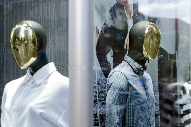 Mannequins masculins et femelles avec des visages de miroir dans la fenêtre de boutique photographie stock libre de droits
