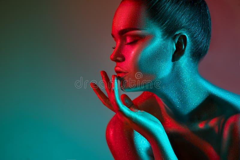 Mannequinvrouw in kleurrijke heldere fonkelingen en neonlichten die in studio, portret stellen van mooi sexy meisje stock fotografie