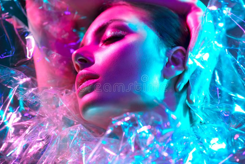 Mannequinvrouw in kleurrijke heldere neonlichten die in studio door transparante film stellen Portret van mooi sexy meisje stock afbeeldingen