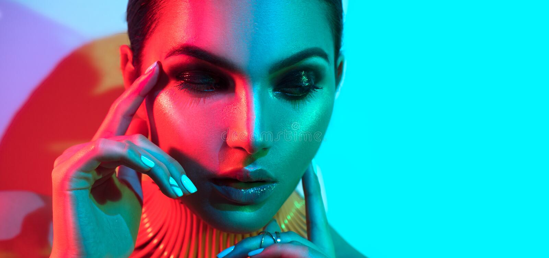 Mannequinvrouw in kleurrijke verstralers met het in make-up en manicure stellen stock foto's