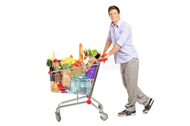 Mannetje dat een boodschappenwagentjehoogtepunt met kruidenierswinkels duwt royalty-vrije stock foto