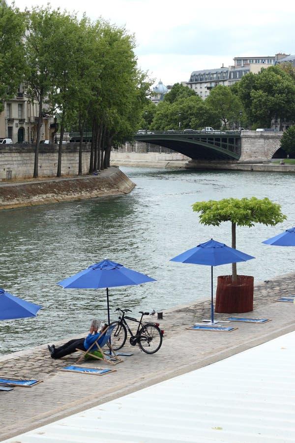 Mannetje dat op een ligstoel naast zijn fiets onder een paraplu dichtbij een waterkanaal legt in de stad royalty-vrije stock fotografie