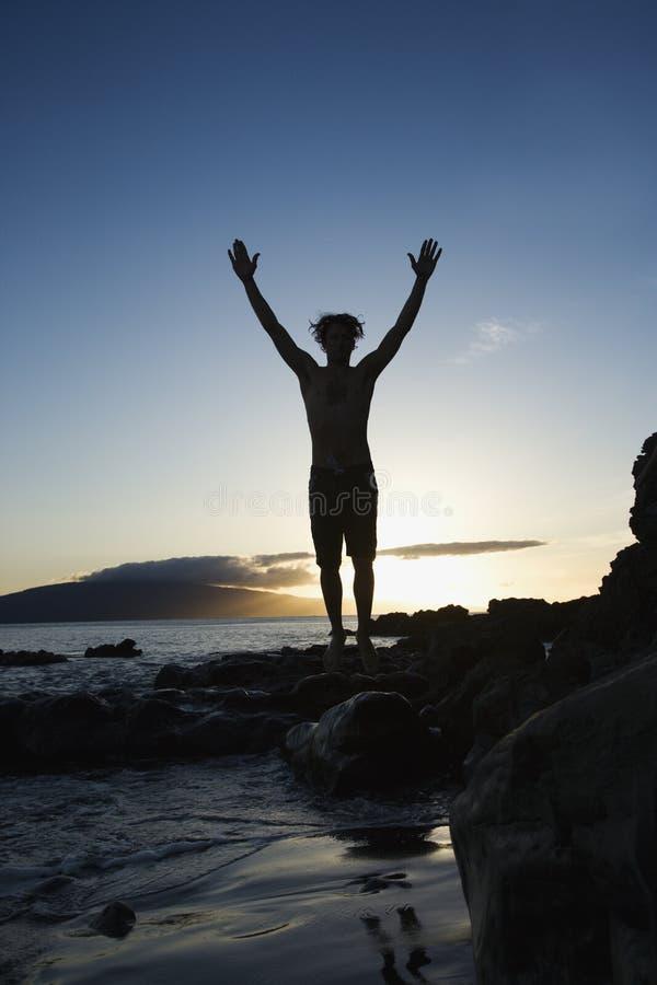 Mannetje dat op strand springt. stock afbeelding