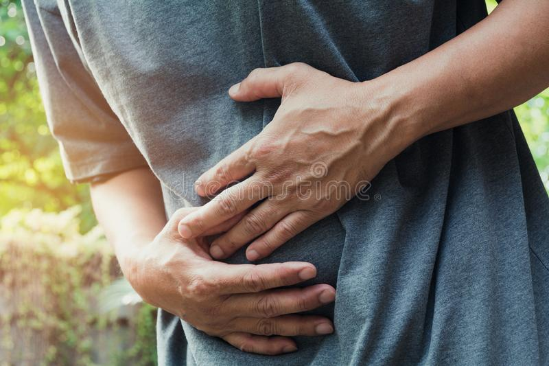 Mannetje die aan maagpijnpijn lijden, a-mensenmaagpijn bij outdoo stock foto