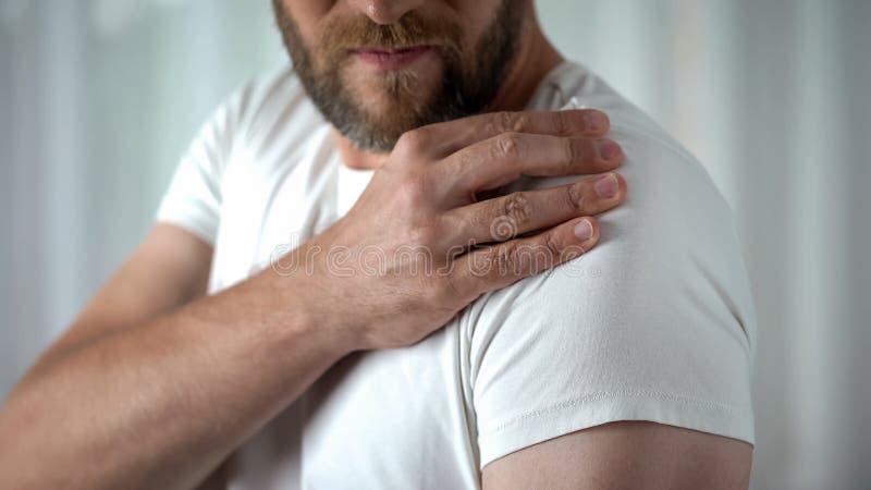 Mannetje die aan schouderpijn lijden, spierpijn, het probleem van de ontstekingsverstuiking stock fotografie