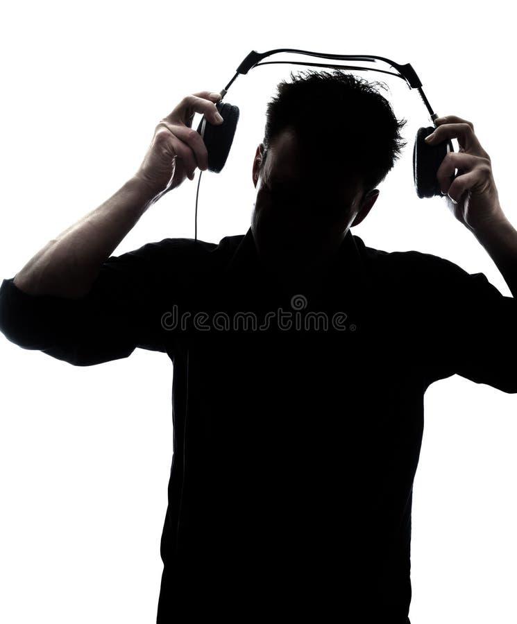 Mannetje die in silhouet hoofdtelefoons zetten royalty-vrije stock afbeelding