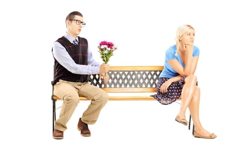 Mannetje die een bos van bloemen en ongeïnteresseerde vrouwelijke zitting geven stock foto