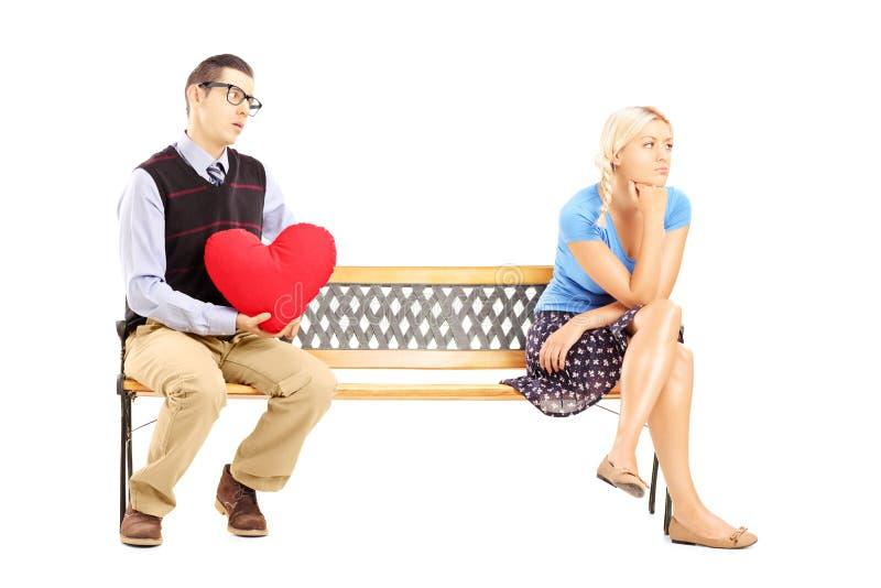 Mannetje die een rood hart en een teleurgestelde vrouwelijke zitting houden stock afbeeldingen