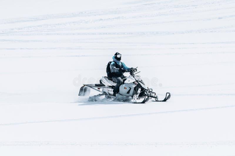 Mannetje die een sneeuwscooter op een groot sneeuwgebied berijden royalty-vrije stock foto's