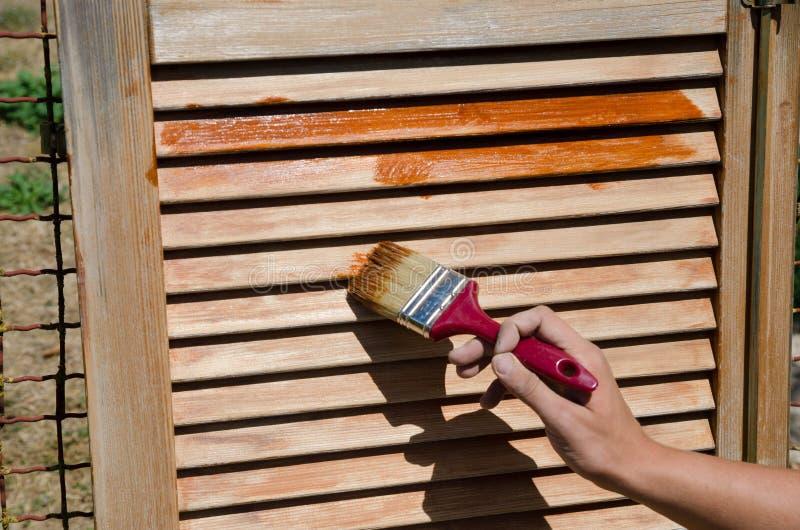 Mannetje die houten Maltees venster schilderen Sluit omhoog stock afbeelding