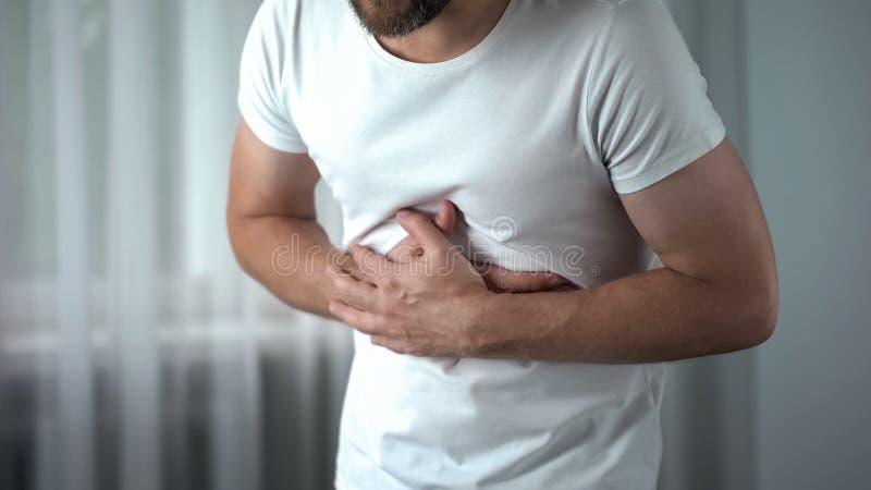 Mannetje die maagpijn voelen thuis, gastritissymptoom, maagzweer, pancreatitis stock fotografie
