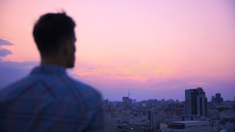 Mannetje die megalopolis van dak die van de bouw bekijken, van majestueuze mening genieten stock foto's
