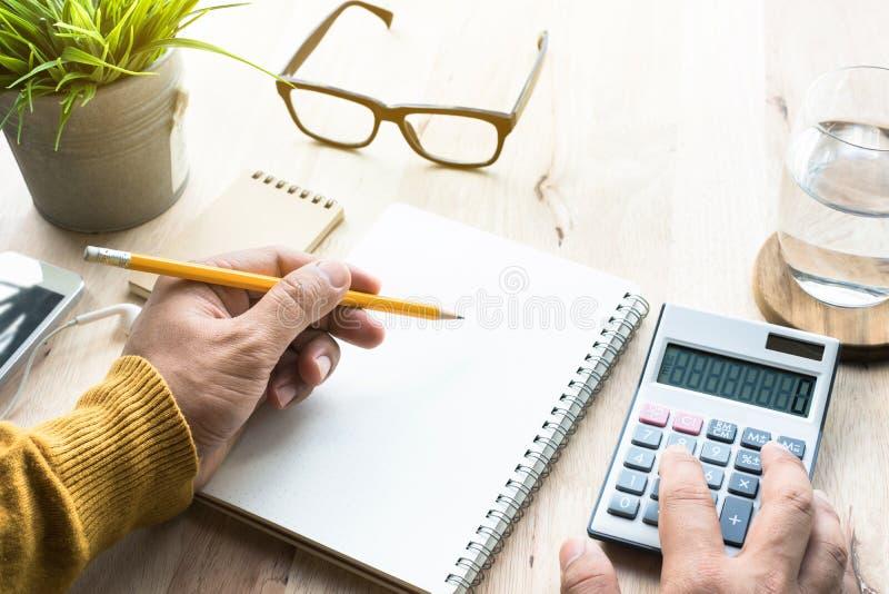 Mannetje die met calculator en blocnote aan worktable werken stock fotografie