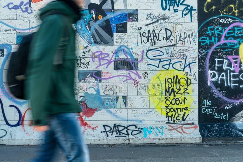 Mannetje die naast het beroemde oriëntatiepunt van Berlijn, de Zijgalerij van het Oosten lopen stock fotografie