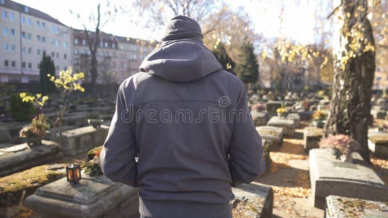 Mannetje die op begraafplaats, die aan ziel van dood lopen, voelend verdriet en pijn spreken royalty-vrije stock foto's