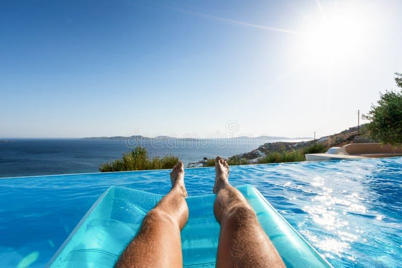Mannetje die over blauw poolwater met mening aan het overzees drijven royalty-vrije stock afbeelding