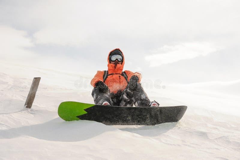 Mannetje die snowboarder onderaan de bergheuvel op de raad berijden Sno stock afbeeldingen