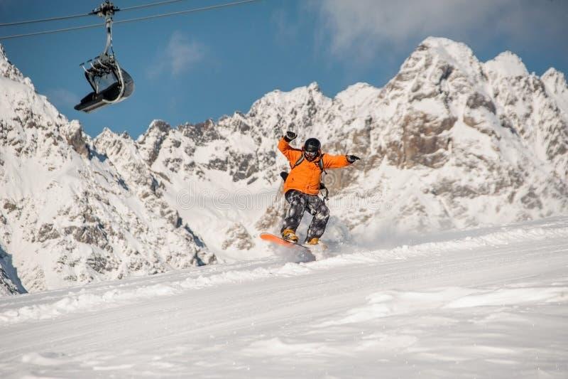 Mannetje die snowboarder op de berghelling springen stock afbeelding