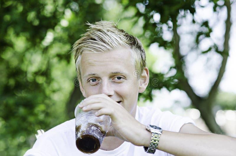 Mannetje die van drank buiten genieten stock foto