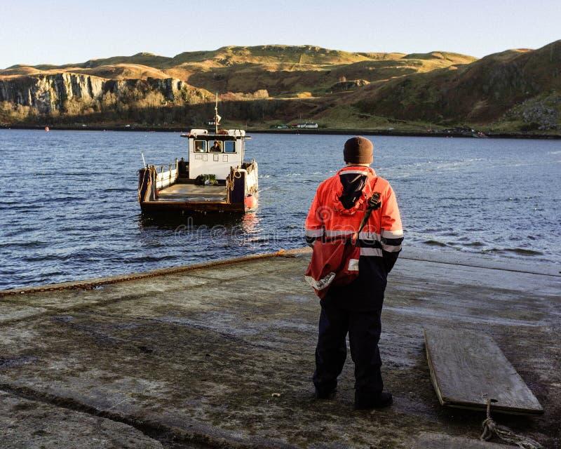 Mannetje die werkkledij dragen die zich op de pijler met boot het opstijgen bevinden stock foto