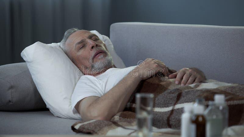 Mannetje die in zijn jaren '60 thuis in bed, pillen en vloeistoffen slapen die zich op de lijst bevinden stock afbeeldingen