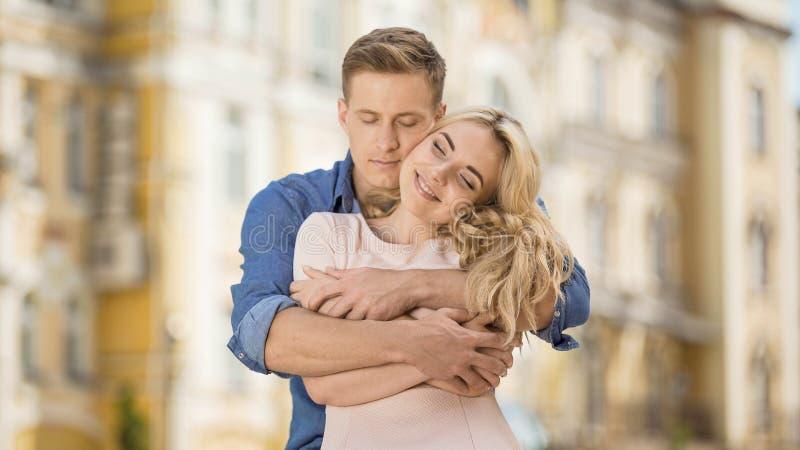 Mannetje die zijn meisje van achter, zoete romantische verhouding, tederheid koesteren stock fotografie