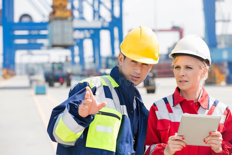 Mannetje en vrouwelijke werknemers die in het verschepen van werf bespreken stock afbeelding