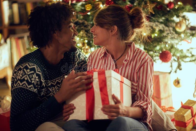 Mannetje en wijfje die Kerstmis ruilen stellen en in vakantie het het genieten van voor royalty-vrije stock afbeeldingen