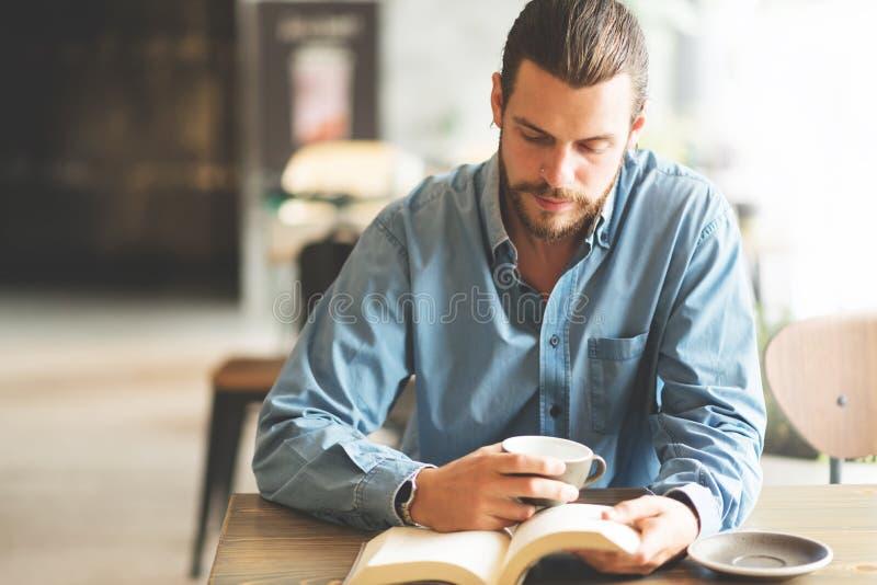 Mannetje freelancer in blauw overhemd die een boek lezen royalty-vrije stock foto's