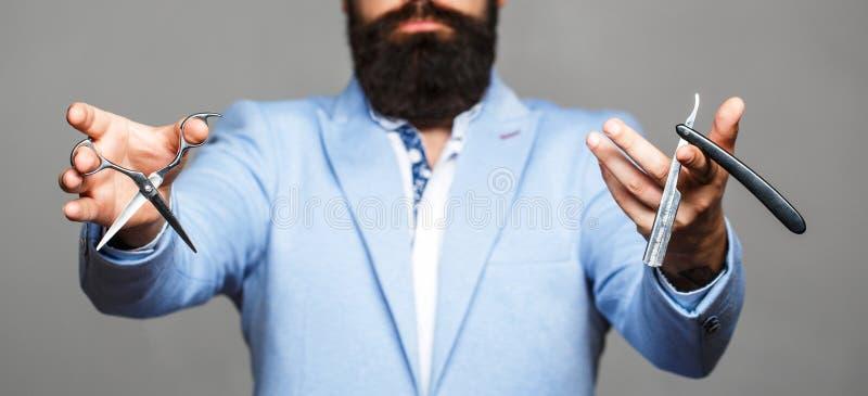 Mannetje in herenkapper Het kapsel van mensen in kapperswinkel Kappersschaar en recht scheermes, kapperswinkel Het kapsel van men stock afbeelding