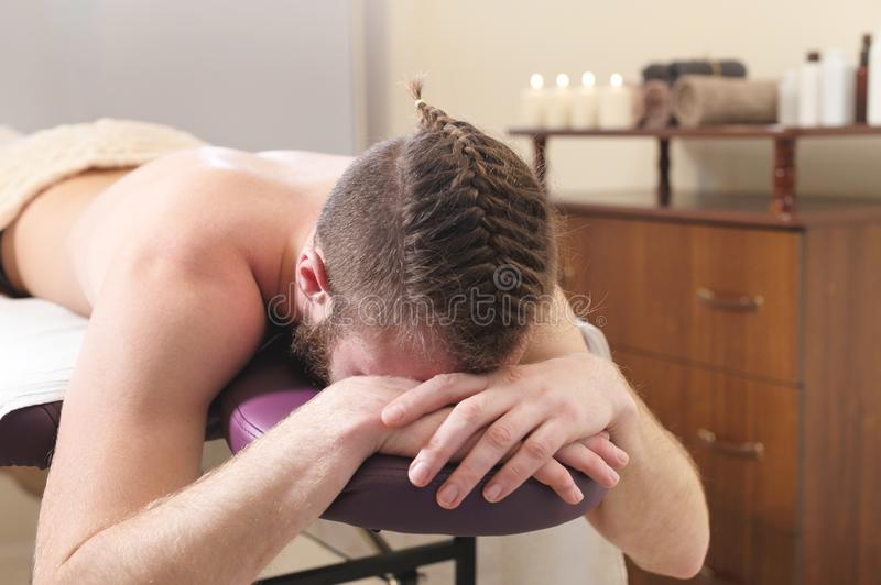 Mannetje hipster met gevlecht in haar en geschoren tempels die op een massagestapelbed liggen onderaan gezicht die en rusten wach stock afbeeldingen