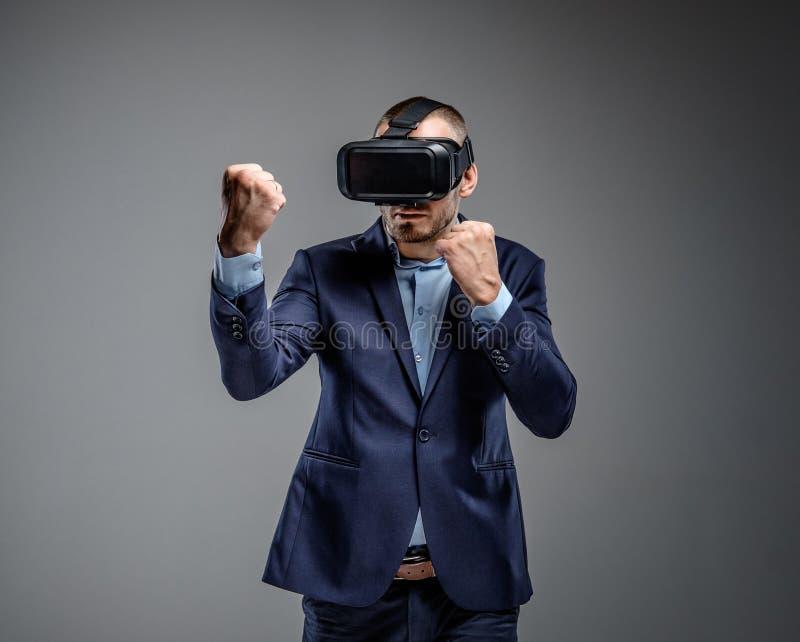 Mannetje in kostuum het vechten met virtuele werkelijkheidsglazen op zijn hoofd stock foto