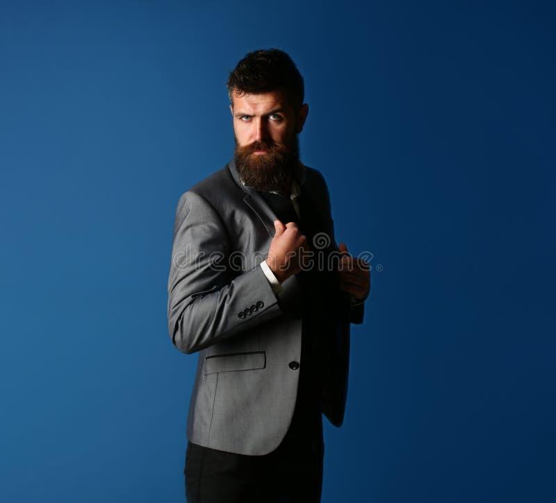 Mannetje in kostuum, mens in smoking, modieuze mens in een doekjasje Knappe gebaarde zakenman in klassiek kostuum Zakenman binnen royalty-vrije stock afbeelding