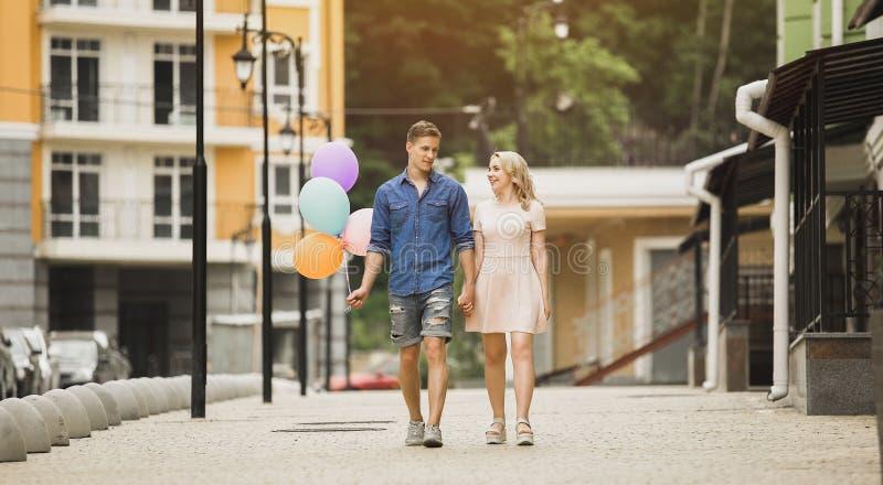 Mannetje met ballons en onderaan straat wandelen en wijfje die, romantische datum spreken royalty-vrije stock afbeeldingen