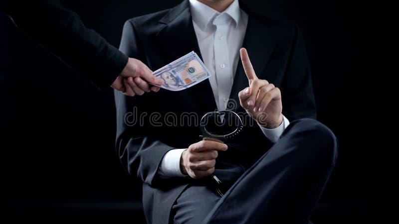 Mannetje met handcuffs die steekpenning, onvermijdelijke straf, onwettige overeenkomst weigeren te nemen stock foto